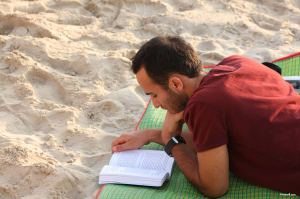 man_reading_book_on_beach-other